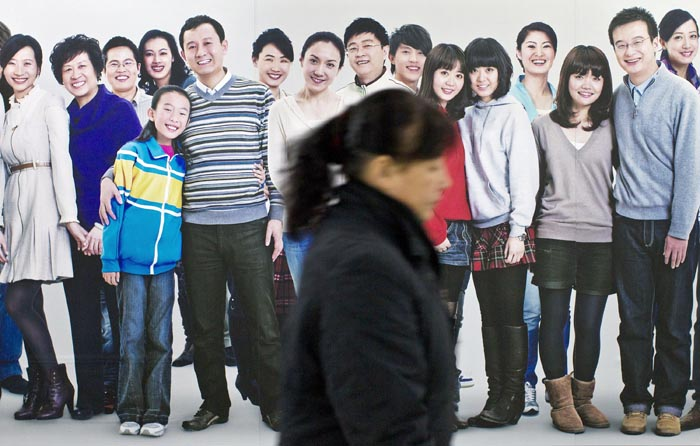 A commuter walks past a billboard of smiling people. Chinese leaders are scrambling to shore up flagging economic growth as exports weaken, abruptly reversing course after they spent two years struggling to cool an overheated expansion and surging inflation.