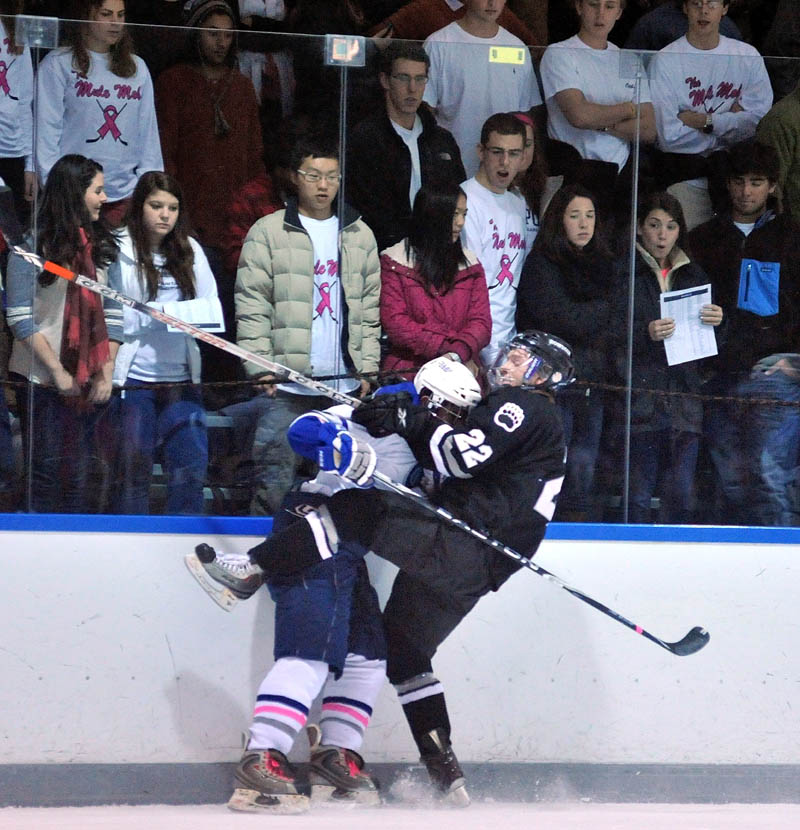 Colby College's Jesse Lehman, left, checks Bowdoin College's Nick Wetzel into the boards during the first period Friday at Alfond Arena in Waterville.