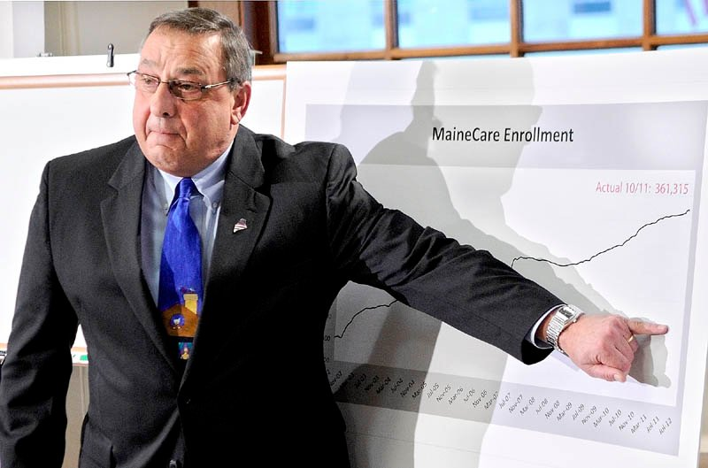2014 FILE PHOTO: Gov. Paul LePage gestures at a graph during a news conference announcing changes to the MaineCare system Tuesday in Augusta. The graph shows the increasing number of residents on MaineCare, now totaling 361,315.