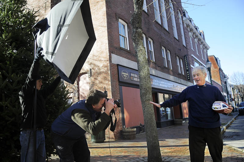 James J. Dineen M.D., right, is photographed Thursday by New Hampshire photographer Bill Truslow, center, as his assistant, Nate Eikelberg, holds a strobe on Water Street in Gardiner for Massachusetts General Hospital (MGH). A Gardiner native, Dr. Dineen is overseeing a new educational collaboration between Maine and MGH to expand the range of health care education programs, materials and opportunities available to providers, patients, families and veterans throughout the state of Maine, according to MGH. Called the James J. Dineen, MD, Maine-MGH Health Education Partnership (MHEP), to honor a long-time MGH primary care physician, the initiative is being funded by a gift from the Lunder Foundation. Dineen is a former Gardiner High quarterback and former team doctor for the Patriots and Bruins.