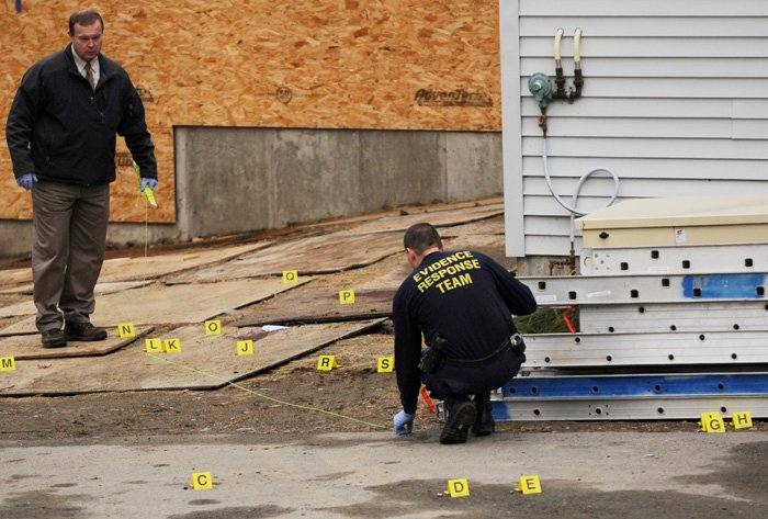 Maine State Police Trooper David Yankowski, left, and another member of the Evidence Response Team investigate the scene of a shooting behind the Hilltop Manor in Dover-Foxcroft on Tuesday. A sheriff's department dispatcher walked into a nursing home and fatally shot a maintenance worker before fleeing to nearby fairgrounds, where he was shot and killed by a state trooper.