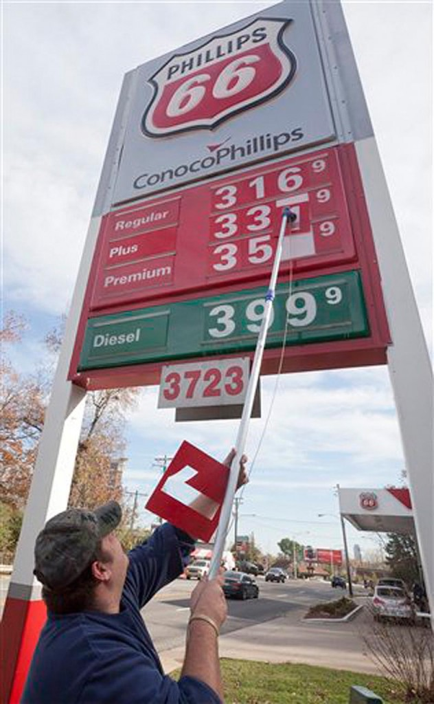 In this Dec. 1, 2011 file photo, store manager Joseph Sublett changes gasoline prices to reflect a three-cent drop at a Little Rock, Ark., Conoco-Phillips station. The U.S. economy is ending 2011 on a roll. Growth in the fourth quarter likely accelerated to the fastest pace since mid-2010, and the job market appears to be strengthening. (AP Photo/Danny Johnston, File)