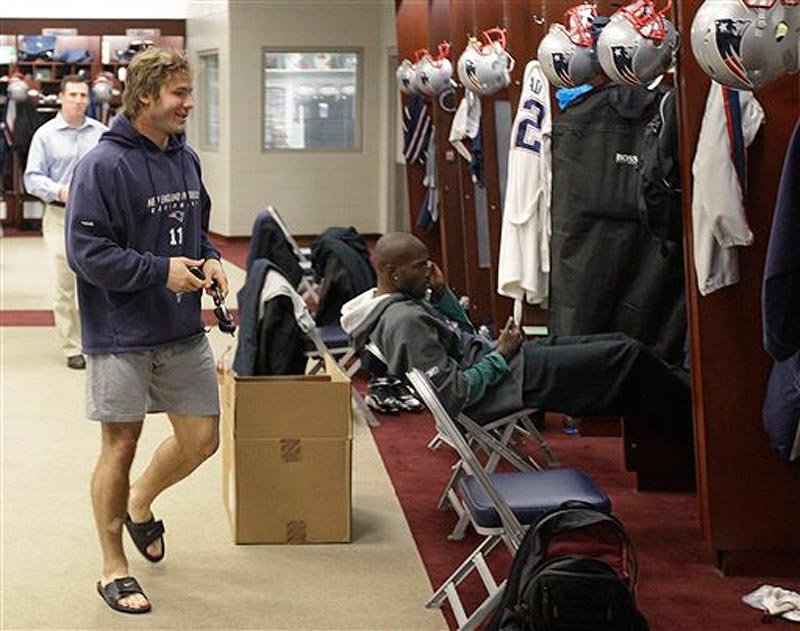 New England Patriots wide receiver Julian Edelman walks through the locker room past Chad Ochocinco, sitting in front of his locker, during a media availability at the NFL football team's facility in Foxborough, Mass., Wednesday morning, Nov. 30, 2011. (AP Photo/Stephan Savoia)