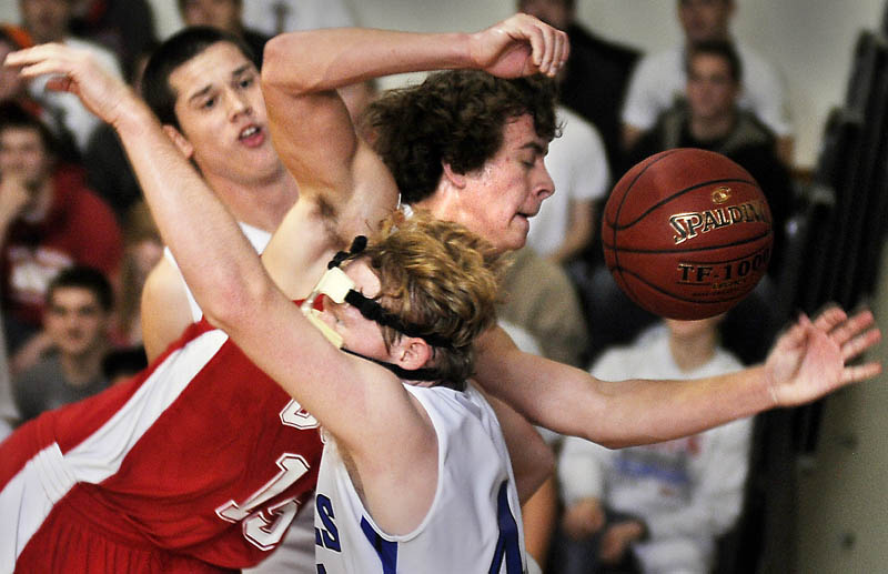 TIGHT SQUEEZE: Cony High School's Josiah Hayward, center, is pinched Thursday between Erskine Academy's Tyler Belanger, right, and Jory Humphrey during a basketball match up in South China.