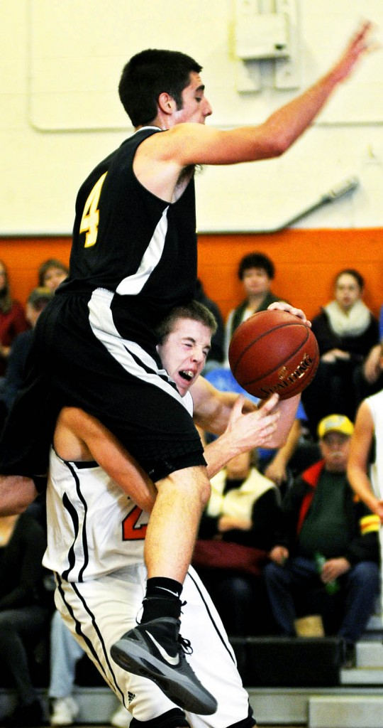 OVER THE TOP: Maranacook Community High School's Seth Miller lands Tuesday on the shoulders of Gardiner Area High School's Matt Hall during a basketball match up in Gardiner.