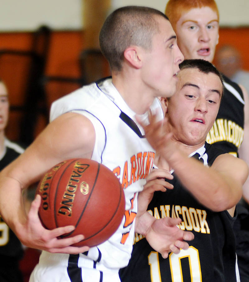 Staff photo by Andy Molloy OVER THE TOP: Maranacook Community High School's Jesse Evans, right, blocks Tuesday Gardiner Area High School's Jake Palmer during a basketball match up in Gardiner.