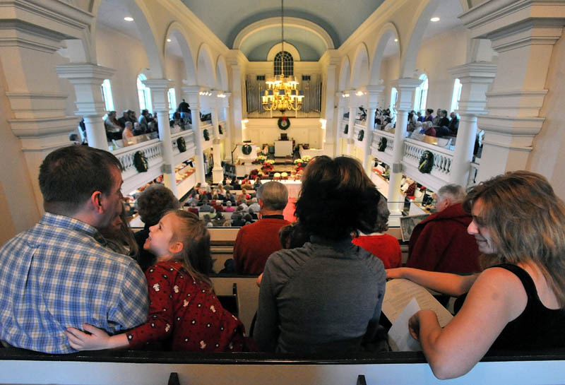 Sean Boyd, far left, has a moment with Lexi Delano, 5, as his wife, Mel, center and Christie Keller, far right, wait for the beginning of the Global Celebration of Christmas service at Lorimer Chapel at Colby College Saturday evening.