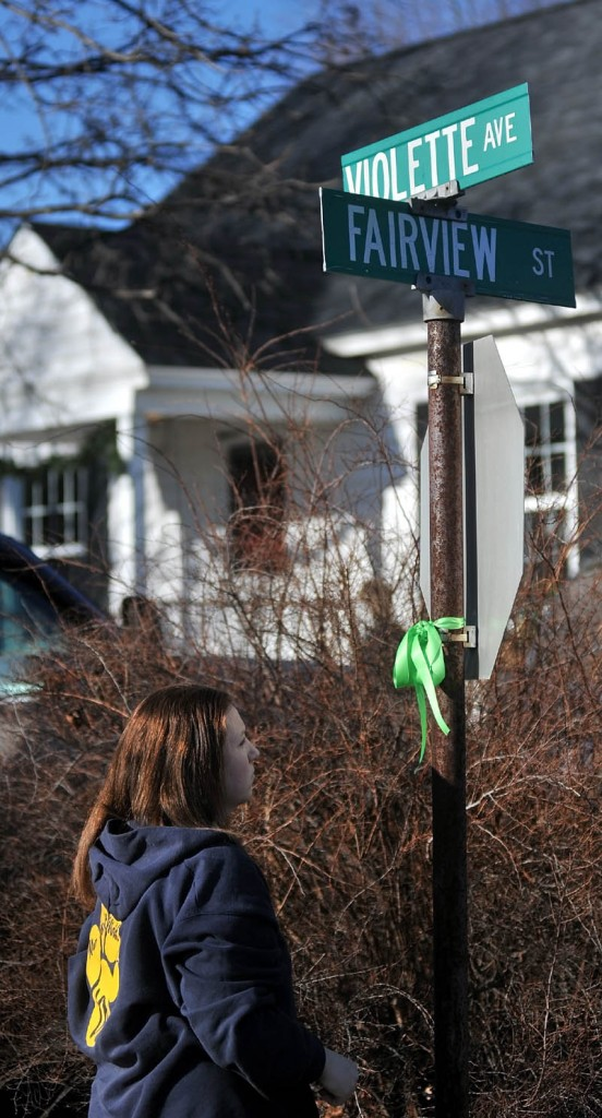 Brandi Wentzel, of Fairfield, hangs a green ribbon on a street sign at the intersection of Fairview Street and Violette Avenue near the home of missing 20-month-old Ayla Reynolds on Thursday.