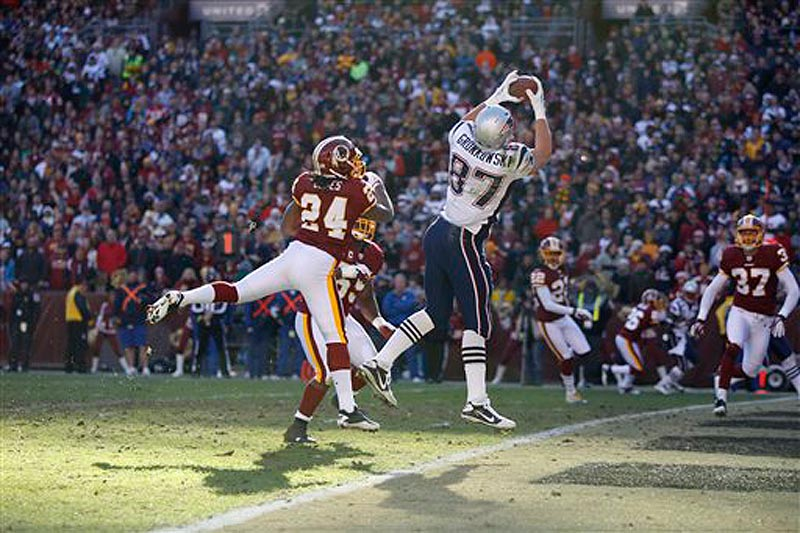 New England Patriots tight end Rob Gronkowski (87) catches a touchdown pass over Washington Redskins strong safety DeJon Gomes (24) during the first half of an NFL football game on Sunday, Dec. 11, 2011 in Landover, Md. (AP Photo/Evan Vucci)