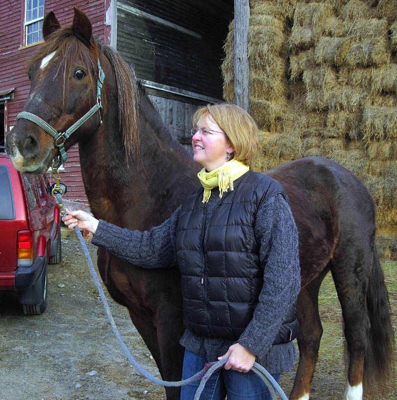 "HUMANE TREATMENT: Janelle Tirrell, a veterinarian with Maine Equine Association, stands with her 25-year-old Morgan stallion. Tirrell, who serves on the state's Animal Welfare Advisory Council, said she isn't in favor of slaughtering horses and favors humane treatment of animals. ""If this can be done humanely, it's certainly better,"" Tirrell said. ""I would rather see a horse go to slaughter than starve to death and freeze to the ground in the winter. I've seen live animals frozen to the ground."""