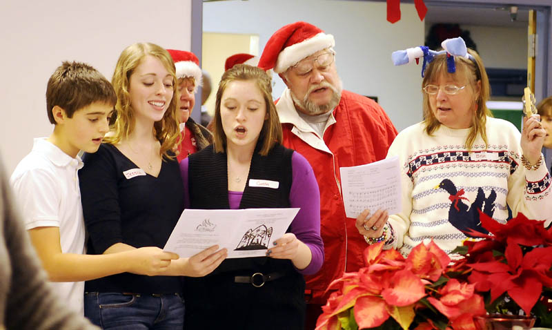 Guests and volunteers sing Christmas tunes Sunday during the community meal served at the Prince of Peace Lutheran Church in Augusta.