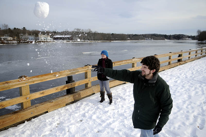 TAKE THAT! Josh Canty and Rachael Harris launch snowballs Tuesday at the boat landing on the Kennebec River in Gardiner. Canty, a resident of the Republic of Mexico, and Harris, a resident of the Marshall Islands, attended Gardiner Area High School together and were flinging snow at their buddy, Jeremy Sales, during a break at home.