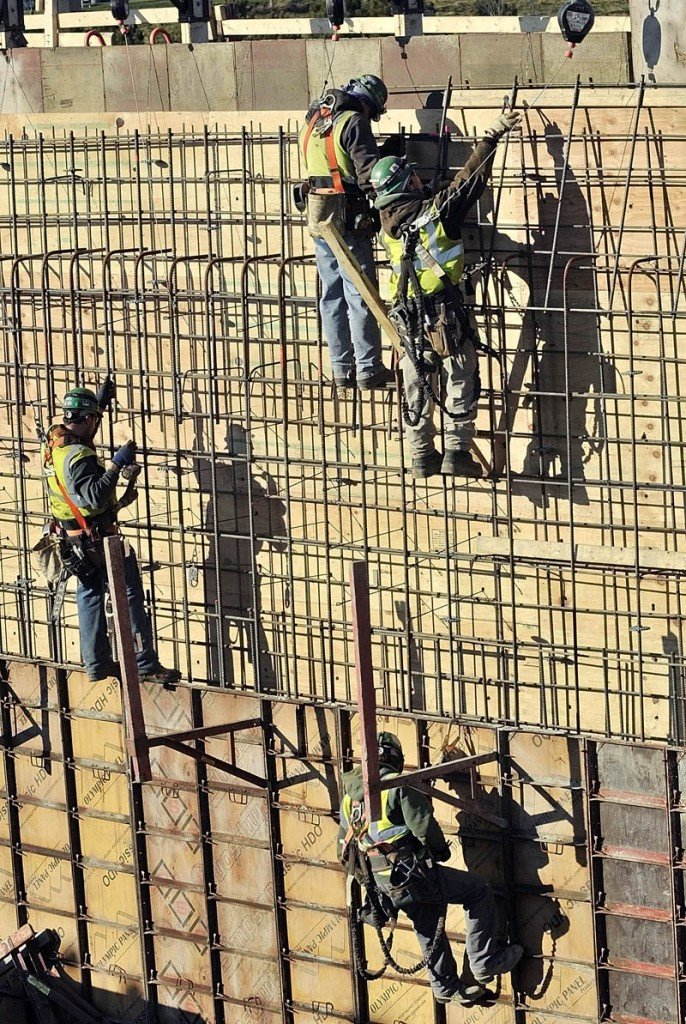 NO FEAR OF HEIGHTS: Newman Concrete Services workers tie together reinforcing bars for a concrete retaining wall Wednesday at the new MaineGeneral regional hospital construction site in Augusta.