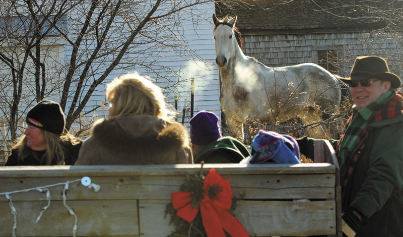 A horse watches a sleigh go by on Oak Grove Road in North Vassalboro during the 2nd annual Cowboy Christmas Parade on Sunday.