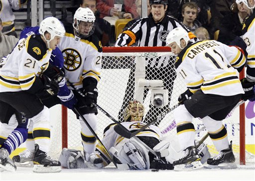 Boston Bruins goalie Tuukka Rask, center, lies on the ice as teammates Gregory Campbell (11), Daniel Paille (20) and Andrew Ference (21) move to clear the puck as Toronto Maple Leafs' Joey Crabb, rear left, looks for a shot in the second period Saturday in Boston.