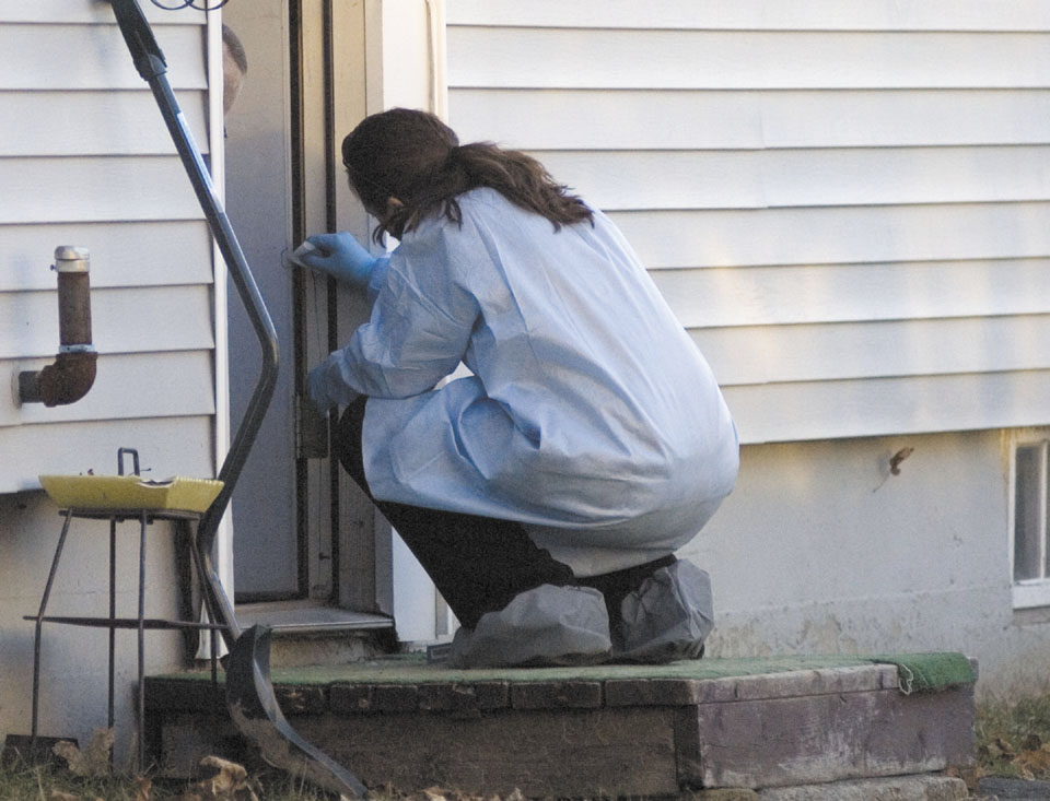 A Maine State Police reconstruction team takes samples Tuesday from the edge of the doorway into the home where 20-month-old Ayla Reynolds was last seen on Violette Avenue in Waterville.