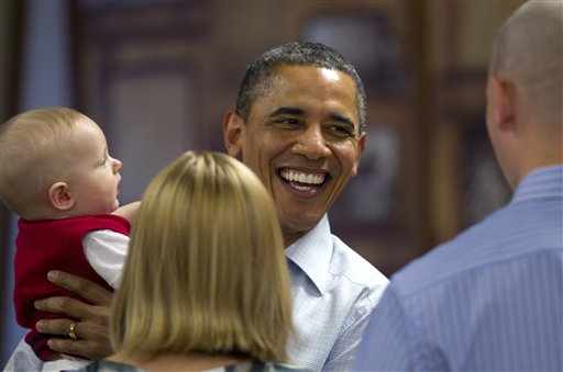 President Barack Obama laughs after getting a mouth full of fingers from Cooper Wall Wagner, 8 months, as he chats with Cooper's parents Captain Greg and Meredith Wagner, as he visits members of the military during Christmas dinner at Anderson Hall on Marine Corps Base Hawaii , Sunday, Dec. 25, 2011, in Kaneohe, Hawaii. (AP Photo/Carolyn Kaster)