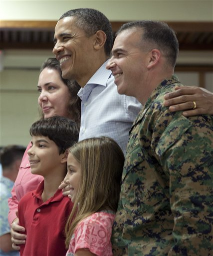 President Barack Obama poses with a military family during a visit to a Christmas dinner at Anderson Hall on Marine Corps Base Hawaii , Sunday, Dec. 25, 2011, in Kaneohe, Hawaii. (AP Photo/Carolyn Kaster)