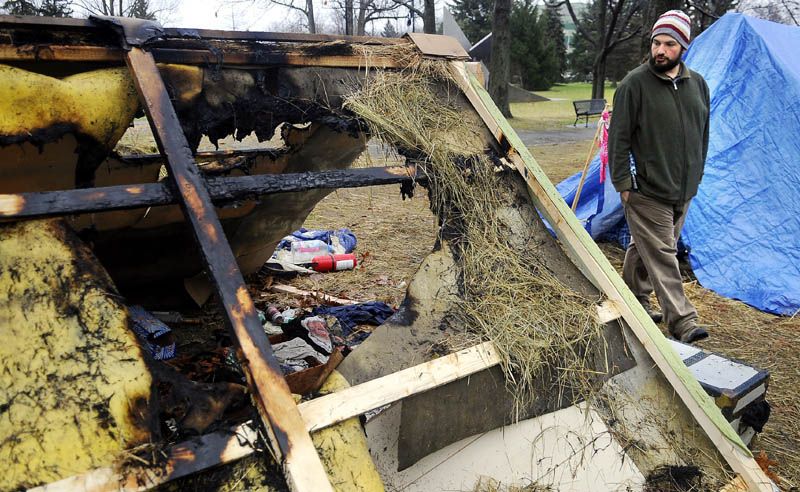 Occupy Augusta movement member Moss Stancampiano walks by a shelter Tuesday morning that burned the previous evening at the group's encampment at Capitol Park in Augusta. Police are investigating the arson which did not injure anyone.