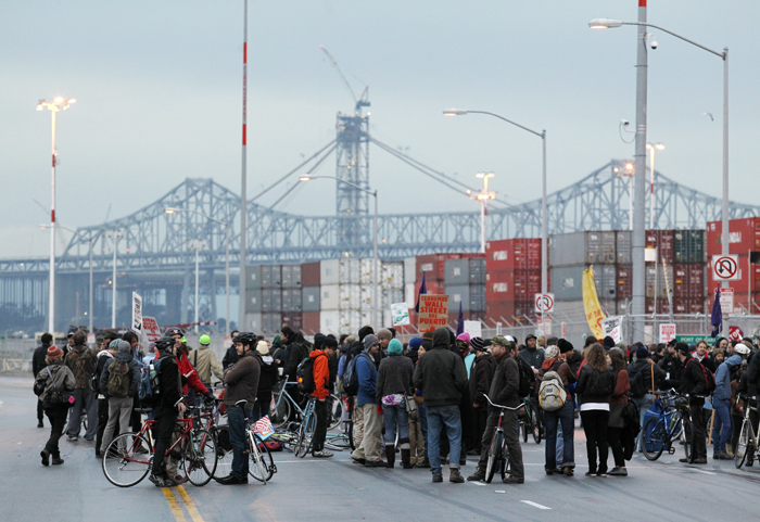 With the San Francisco-Oakland Bay Bridge in the background Occupy protesters block one of the entrances to the Port of Oakland today, in Oakland, Calif.