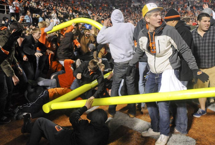 Fans tear down a goal post, injuring some participants, after Oklahoma State's defeat of Oklahoma in Stillwater, Okla.