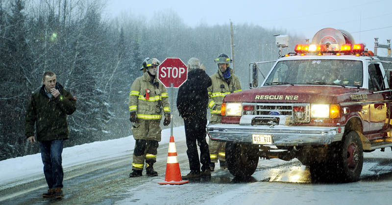 People wait Sunday for volunteer firefighters to re-open Route 3 in Palermo after two vehicle accident claimed the lives of four people. Firefighters shut the road and bypasses through Palermo while the accident was reconstructed.