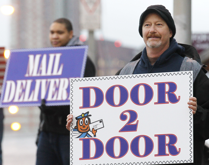 Tom Richardson, right, from the National Association of Letter Carriers, protests in, Portland, Ore., last Wednesday against possible service and staffing cuts. The Postal Service, founded in 1775, may go into default on Dec. 16 unless the government intervenes in some way. Postal Service officials say the operation is in debt $5 to $10 billion, depending on how the numbers are crunched.