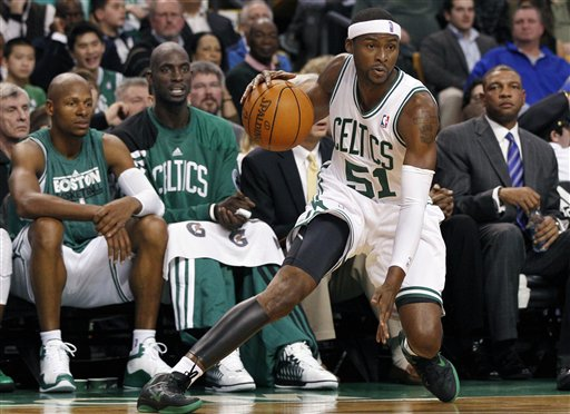 Boston Celtics guard Keyon Dooling (51) handles the ball as teammates, from left, Ray Allen, Kevin Garnett, and head coach Doc Rivers, right, watch from the bench during the first half Wednesday against the Toronto Raptors in Boston.