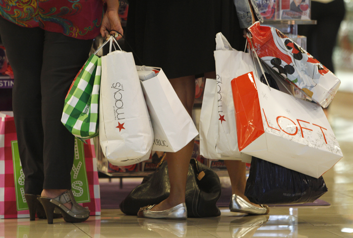 Shoppers stop to look at a display at Dadeland Mall in Miami recently, Americans spent more on autos, furniture and clothing last month as retail sales rose for the sixth straight month.