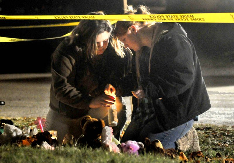 Staff photo by Michael G. Seamans Heather Mirucki, left, and Ashley Tenney, right, lights candles at a teddy bear shrine in front of the home of missing toddler, Ayla Reynolds, on Violette Avenue in Waterville Thursday night. Reynolds was reported missing Saturday.