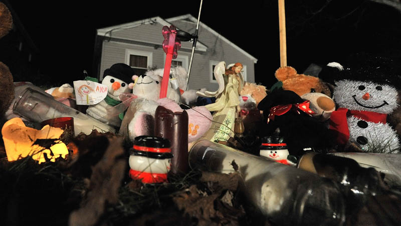 A teddy bear shrine sits outside the Violette Avenue residence of Ayla Reynolds in Waterville Thursday night.