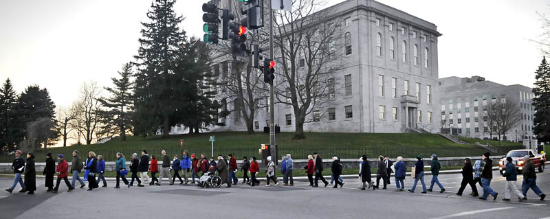 Members of local church congregations walk Sunday past the Capitol in Augusta during a silent march to show solidarity with Occupy Augusta members at Capitol Park.