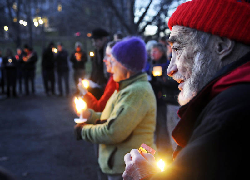 Charles Acker, of Whitefield, holds a candle Sunday during a vigil with members of several local church congregations to show solidarity with the Occupy Augusta members at Capitol Park in Augusta.
