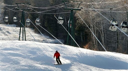 In this photo taken Monday Dec. 12, 2011, empty gondolas sit parked above a lone skier on an open trail at Loon Mountain ski area in Lincoln, N.H. Warm temperatures have continued to hover above optimal snowmaking levels, making for a late start to the ski season in the Northeast. (AP Photo/Jim Cole)