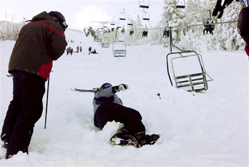 In this Dec. 28, 2010 file photo, a skier comes to help a skier who fell onto the slope after a chair lift derailed at the Sugarloaf ski resort in Carrabassett Valley, Maine. The 35-year-old chairlift that malfunctioned a year ago has now been replaced at a cost of $4 million. (AP Photo/Jack Michaud, File)