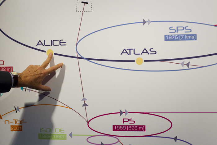 In this May 20, 2011, photo a physicist explains the Atlas experiment on a board at the European Center for Nuclear Research, CERN, outside Geneva, Switzerland. The illustration shows what a Higgs boson may look like in Atlas.