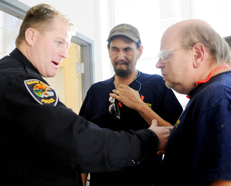 Idaho Falls, Idaho, Police Officer Malin Reynolds, left, shows Tex Tech Industries employee Bill Czerepanyn, right, and Frank Patten the spot where a bullet struck his chest vest during an open house at the Monmouth company Monday. Reynolds, who was shot in June 2011, credits the components in his body armor created by Tex Tech with saving his life.