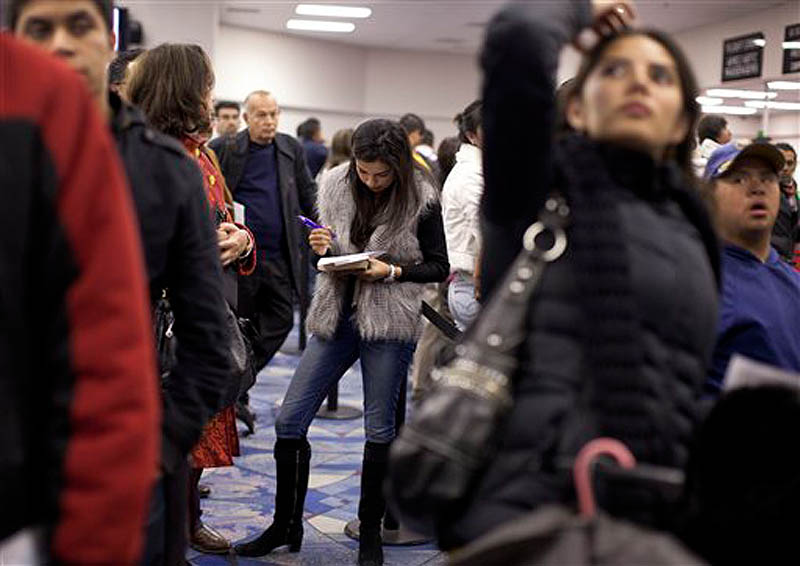 Non-resident visitors from an international flight fill out customs forms while waiting in line at immigration control at McCarran International Airport, Tuesday, Dec. 13, 2011, in Las Vegas. (AP Photo/Julie Jacobson)