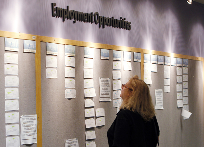 A woman looks at posted employment opportunities at a Denver employment office.
