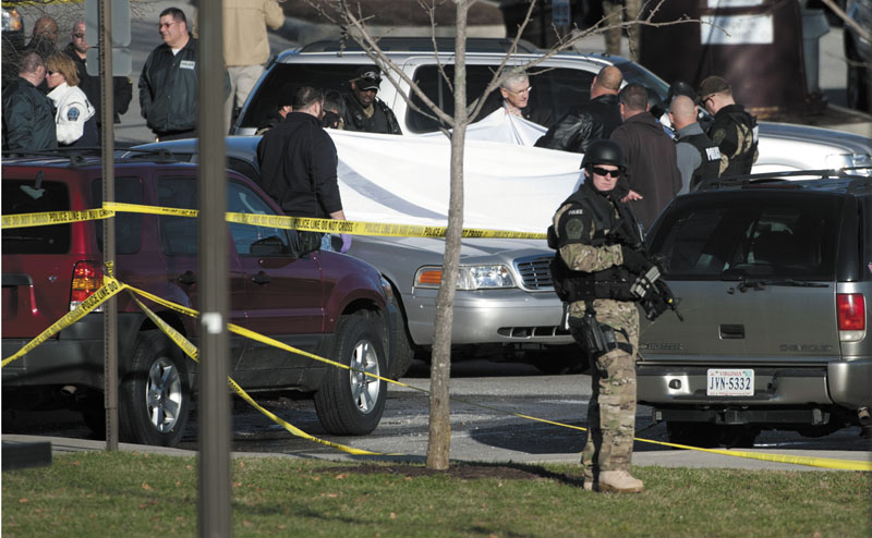 Authorities examine the body Thursday of a police officer shot to death in a parking lot on the campus of Virginia Tech in Blacksburg, Va.
