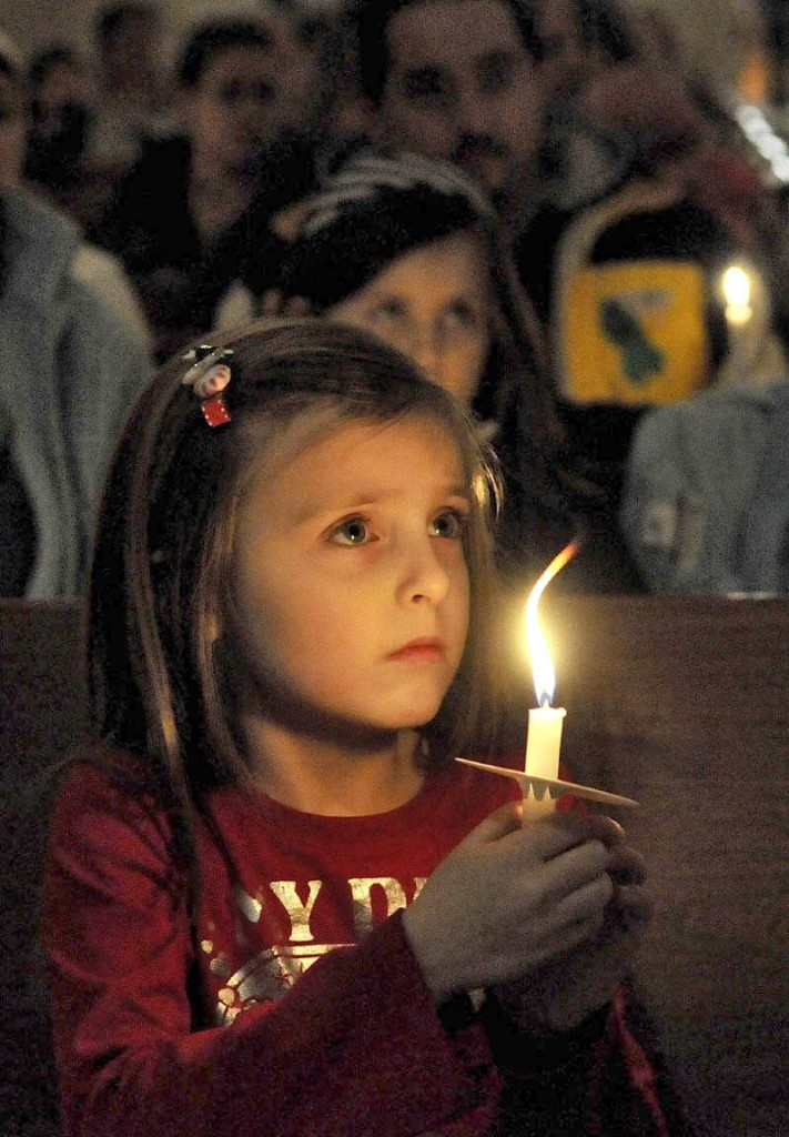 Katy Taylor, 5, holds a candle during the Vigil Of Hope For Ayla Reynolds organized by The Mainely Moms & Dads Wednesday evening in the First Congregational Church in Waterville.