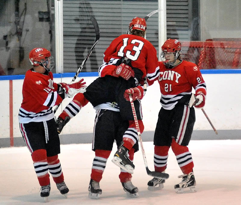 JUMPING FOR JOY: Cony High School's Galen Casey (13) jumps into the arms of teammate Kiefer Cantara as teammates Zach Gagne, left, and Dakota Bowie watch after the Rams scored a goal against Waterville Senior High School on Wednesday in the first period at Alfond Rink at Colby College in Waterville.