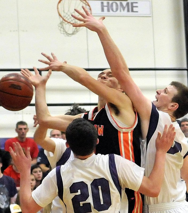 Winslow High School's Brandon Labrie, center facing, is fouled by Waterville High School's J.P. Michaud, right, as teammate Brandon Braley tries to defend in the second quarter at Waterville Senior High School Friday night.