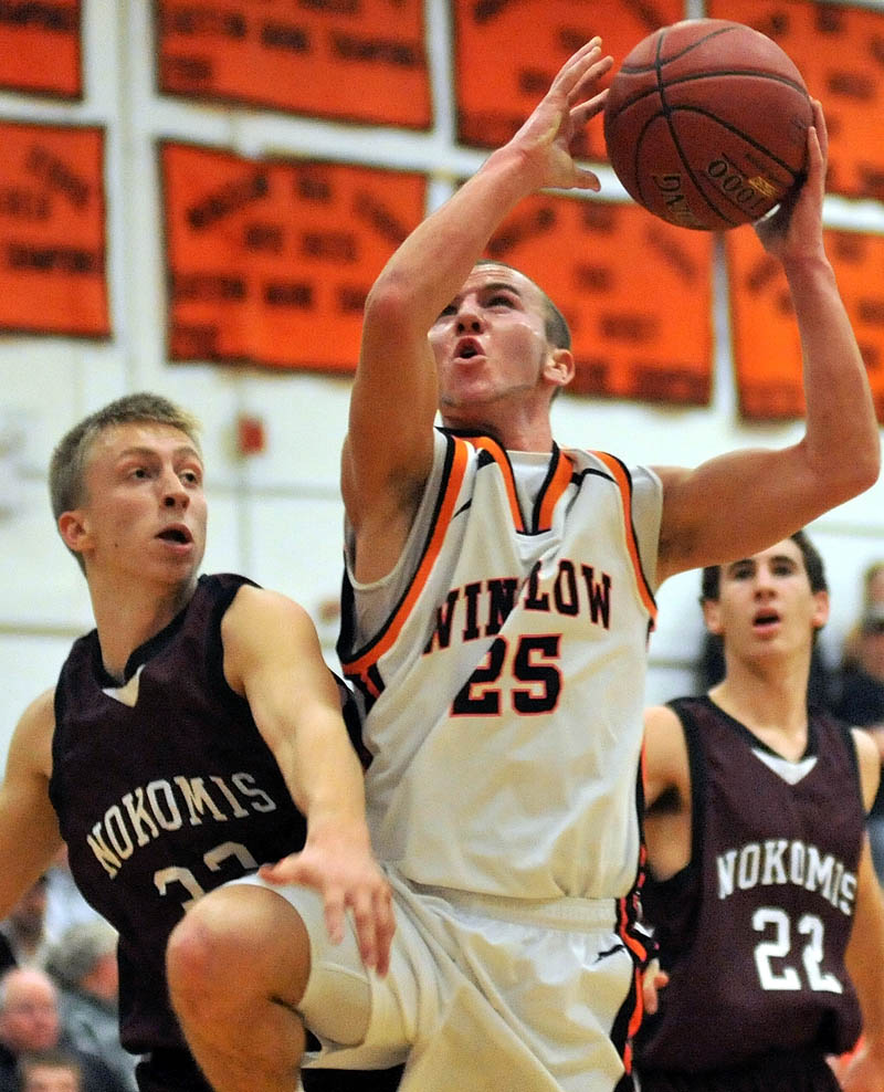 Winslow High School's Justin Murry, center, draws a foul from Nokomis Regional High School's Drew Wing, left, during the first quarter Friday night in Winslow.