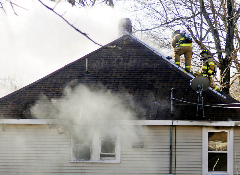 Firefighters ventilate the roof of a Winthrop house that burned on Tuesday.