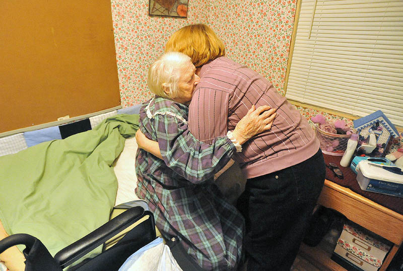 Staff photo by Michael G. Seamans Cheryl helps her mother to bed at the end of the day on December 8, 2011.