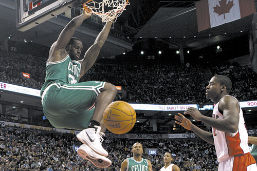SLAM IT DOWN: Boston's Brandon Bass, left, hangs from the basket after scoring as Toronto's Amir Johnson looks on during the first half of a preseason game Sunday in Toronto.