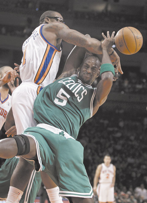 TOUGH GUYS: New York Knicks forward Amare Stoudemire, left, gets tangled up with Boston Celtics power forward Kevin Garnett (5) in the first half Sunday at Madison Square Garden in New York.