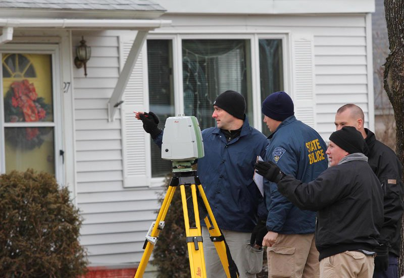 Photo by Jeff Pouland CONTINUING THE INVESTIGATION: Standing in a neighbor's yard, authorities continue their investigation into the disappearance of Ayla Reynolds near her home on Violette Avenue in Waterville on Friday.