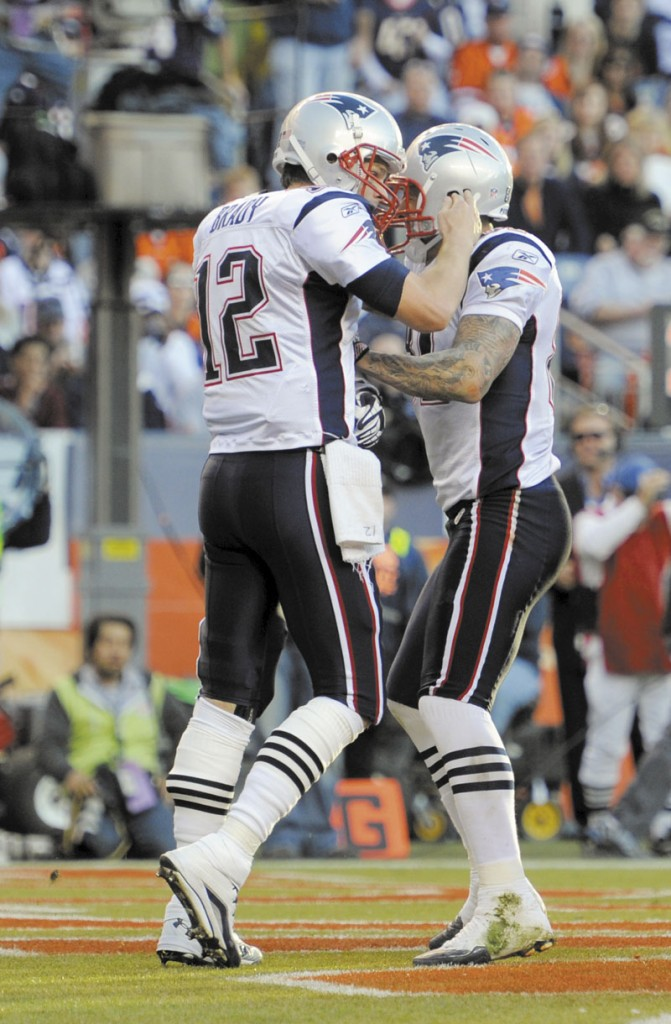 ONE TITLE DOWN: New England Patriots quarterback Tom Brady, left, celebrates with tight end Aaron Hernandez during the Patriots' 41-23 win over the Denver Broncos on Sunday. With the win, New England clinched its ninth AFC East title in 11 seasons.
